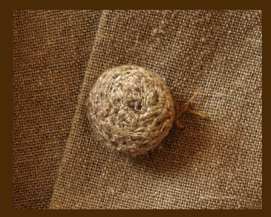 Crocheted button made from fabric ravelings and gold thread