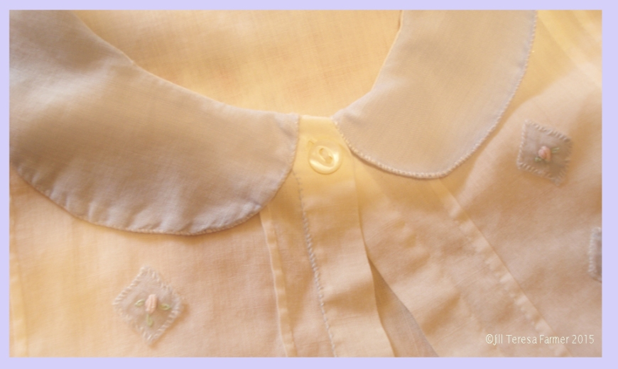 One of grandmother's tiny pearl buttons on a baby dress she made in the 1920s. ©Jill Teresa Farmer